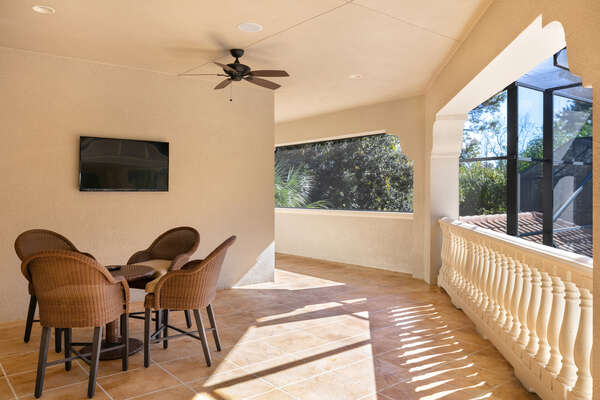 The second-floor patio features comfortable seating and an outdoor TV