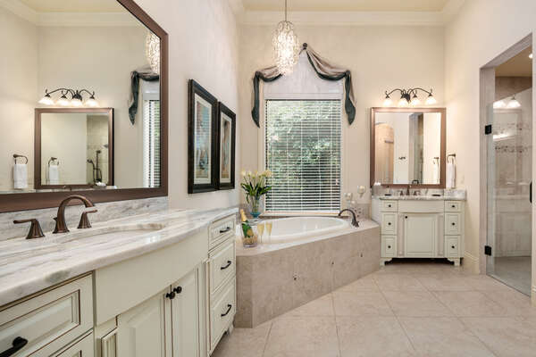 The master en-suite bathroom features his and hers vanity, garden tub, and walk-in shower