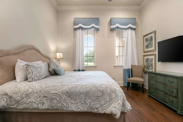 A first-floor king sized bedroom with double doors and TV