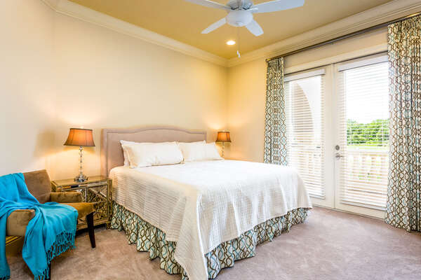 This master suite has a king size bed, access to balcony, and en-suite bathroom