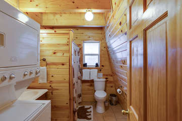 Main level bathroom with shower and full size stack washer and dryer.