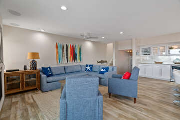 The living room has a large sectional and flat screen Smart TV.