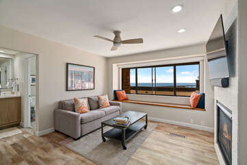 Master sitting area with a view, fireplace, pull-out couch and a wall mounted flat screen Smart TV