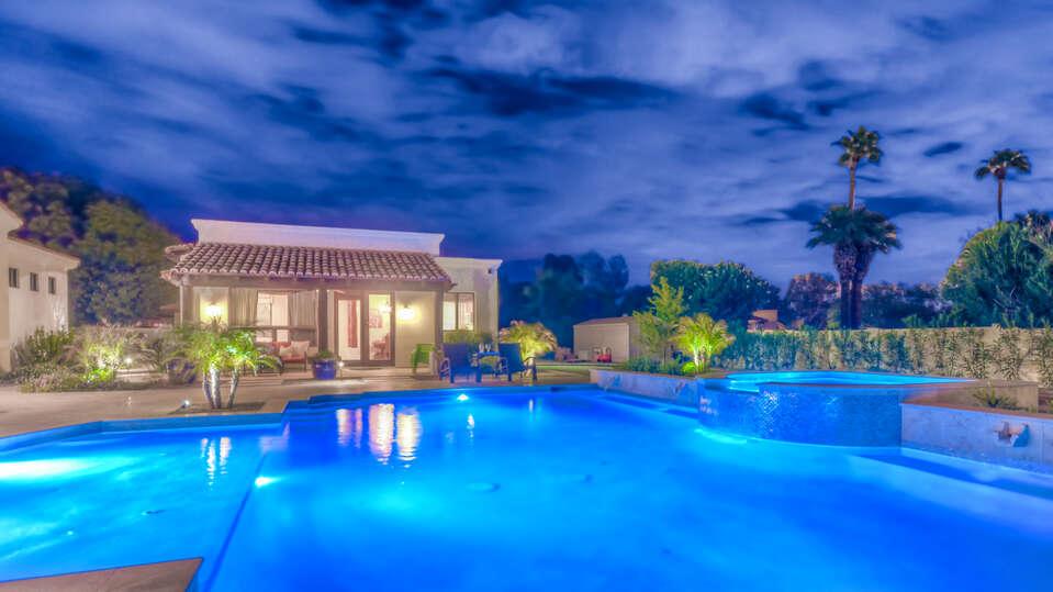 Large Pool Beautifully Lit at Night in Backyard.