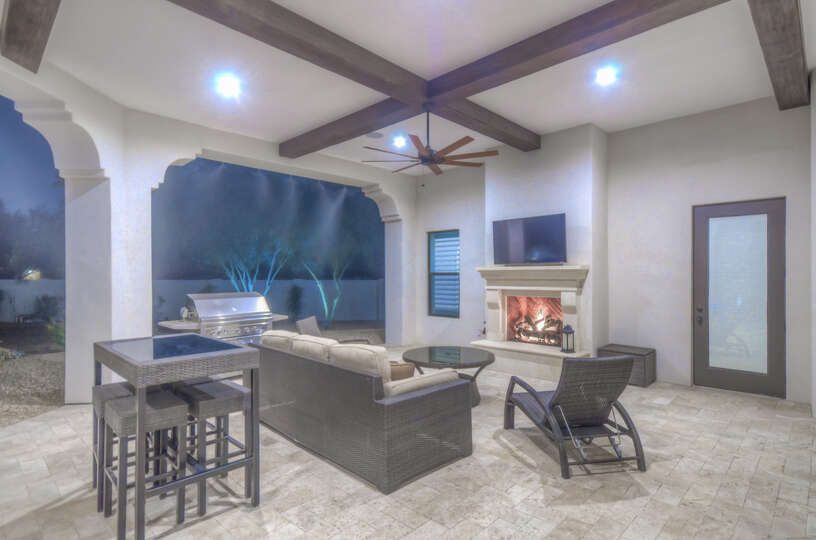 Spacious Outdoor Patio with Couch and TV Mounted on Wall.