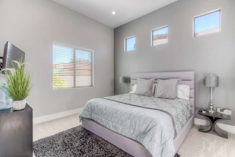 Large Guest Bedroom with Tall Ceilings and Natural Light.