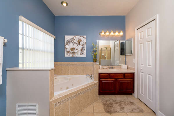 This bedroom has a bath tub, shower & vanity unit and a jacuzzi bath