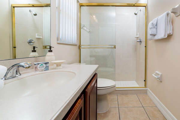 This bedroom has a walk-in shower, toilet and a vanity sink unit.