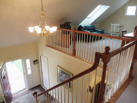 Top of the stairway looking over the entry and loft area - 2 Mashpa Road Harwich Cape Cod - New England Vacation Rentals