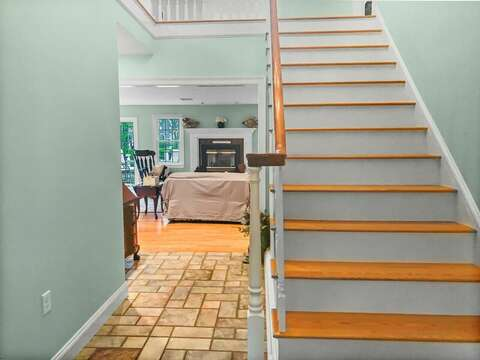 Main stairway to the 2nd floor and a view of the living area - 2 Mashpa Road Harwich Cape Cod - New England Vacation Rentals