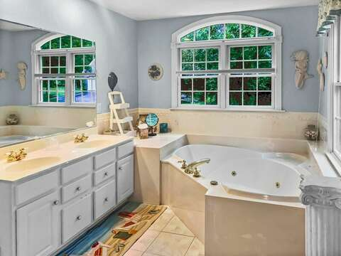 The en suite bathroom to the master bedroom has a jetted tub, separate shower, and double vanity - 2 Mashpa Road Harwich Cape Cod - New England Vacation Rentals