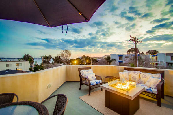 Rooftop patio with fire pit, BBQ, and comfortable outdoor furniture