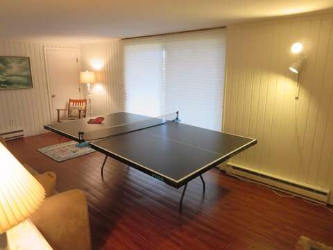 Lower level game room with a ping pong table and sliders to the backyard - 84 Cranberry Lane Chatham Cape Cod - New England Vacation Rentals