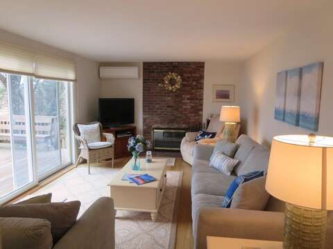 Living room with comfy furniture and sliders to large back deck overlooking the water - 84 Cranberry Lane Chatham Cape Cod - New England Vacation Rentals
