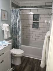 Hall bath is also conveniently accessible to the guest bedroom.  Newly renovated tub and shower with stylish subway tile and beautiful sea glass inset shelves.