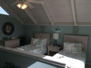 Loft bedroom provides two twin size beds and the decor continues the soothing coastal theme.