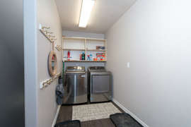 The laundry room features a full sized washer and dryer