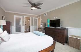 TV and ceiling fan in master bedroom.