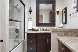 Hallway bathroom with laundry and folding counter.
