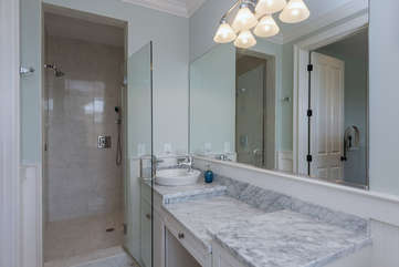 The large bath has marble counters and large tiled walk-in shower with multiple shower heads for the kids.