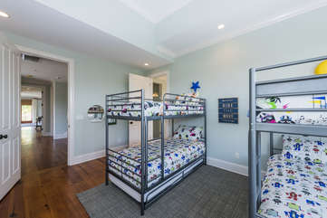 The third bedroom on the second floor has two sets of twin bunks with trundles, HDTV, gaming system, and large private bath.