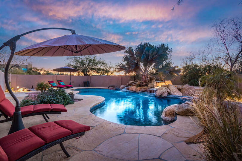Beautiful pool area with spa and seating.