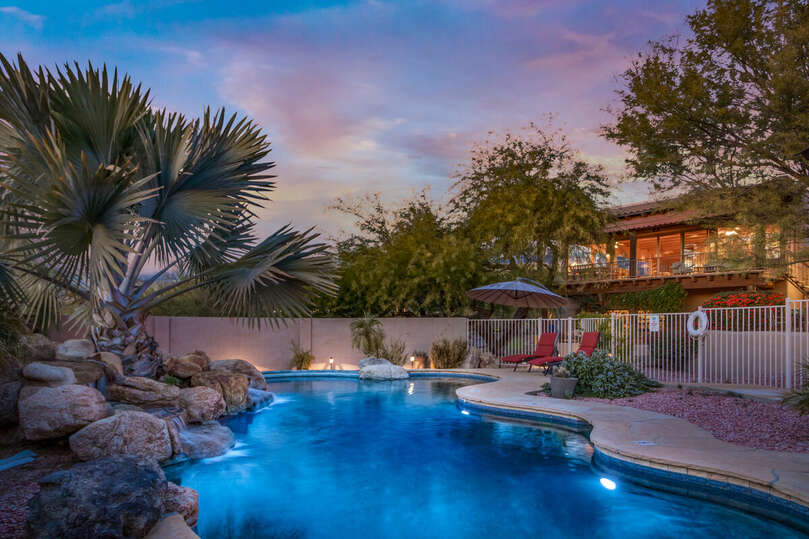 Fenced pool area with spa, seating and lighting.