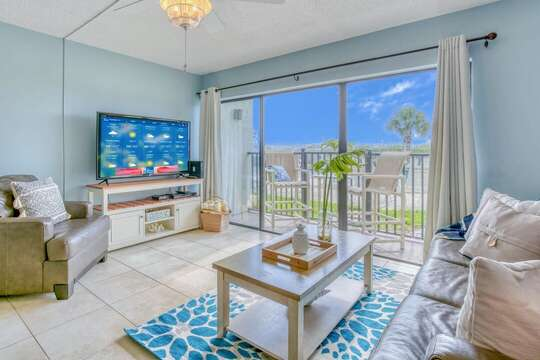 Comfortable and bright living area with a big screen TV