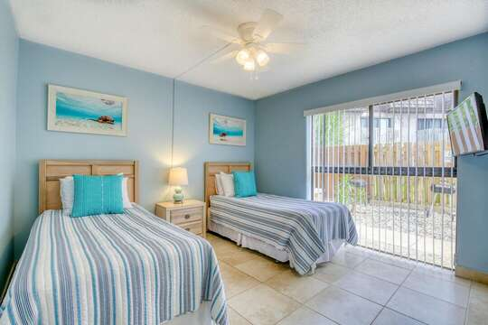 Guest bedroom with two twin beds and a TV