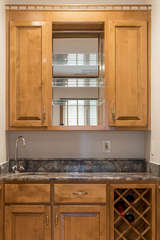 A lovely wet bar with granite counter and wood cabinets.