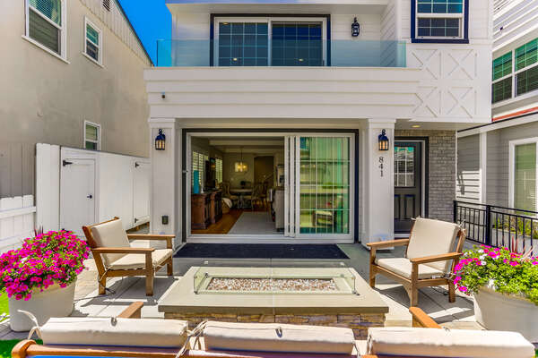 Ground floor patio of this Vacation Home Rental in San Diego with ample seating and fire pit.