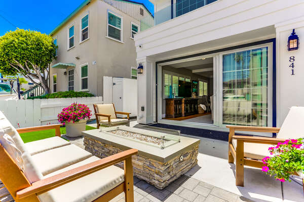 Ground floor patio of this Vacation Home Rental in San Diego with fire pit and seating.