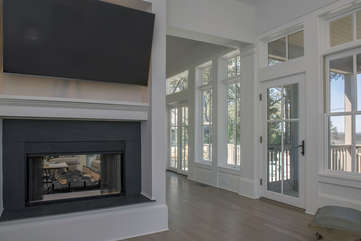 Deck access and 2 sided fireplace with tv in adjacent sitting room