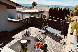 REAR UPSTAIRS BEDROOM ROOFTOP DECK WITH AN OCEAN VIEW