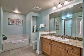 Master bathroom with double vanity, large soaking tub, and glass stand up shower