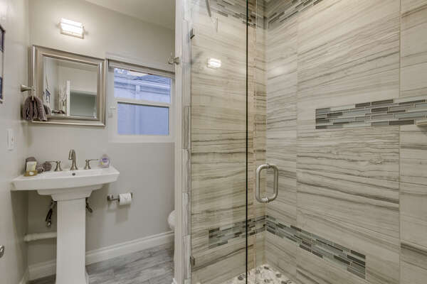 Pedestal Sink, Mirror, and Shower with Glass Doors.
