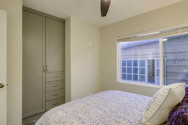 Bedroom with Large Bed, Ceiling Fan, Closet with Drawers.