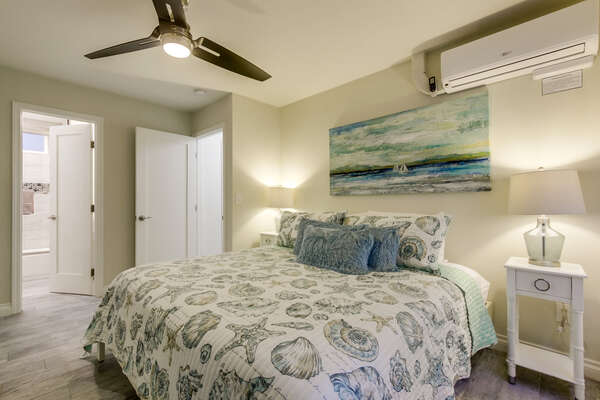 Bedroom with Large Bed, AC, Ceiling Fan, and Nightstand.