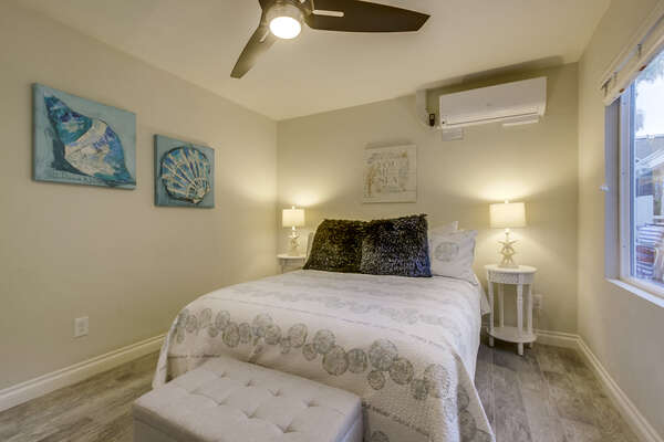 Large Bed, Nightstands, Table Lamps, AC, Ceiling Fan, and Window.