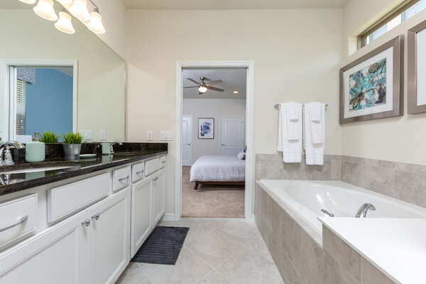 En suite master bathroom with walk-in shower and separate bathtub with private access to the pool area