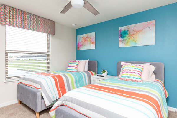 A colorful twin/twin bedroom that is perfect for the kids to rest in