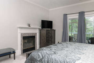 The master has a fireplace, flat screen TV and sliders leading to the enclosed sun room.