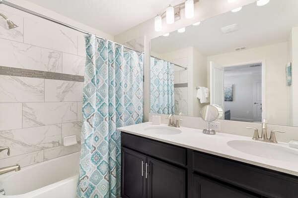 The en-suite bathroom has dual vanity and shower/tub combo