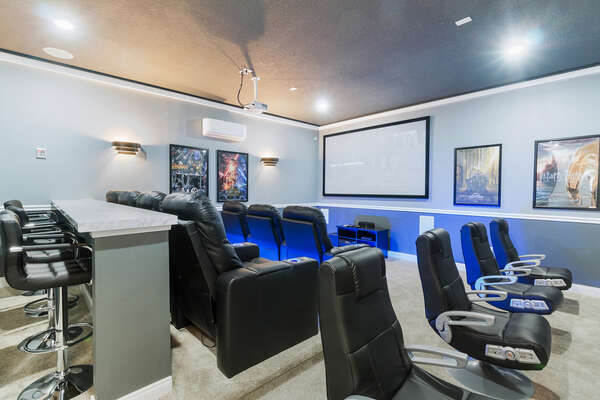 A custom built games/theater room with a 110-inch projection screen and ample seating