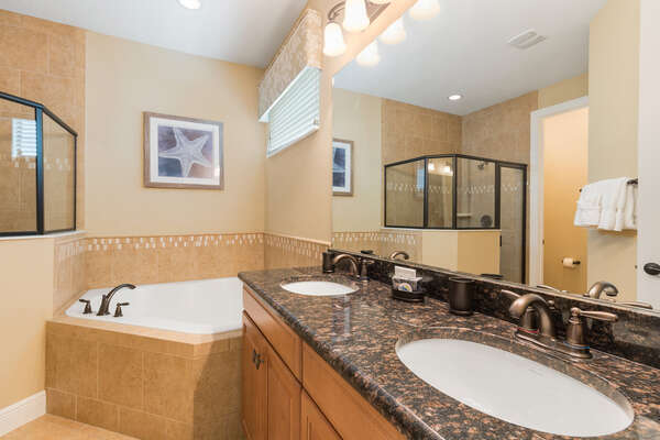 The en-suite bathroom features a dual vanity, walk-in shower, and garden tub