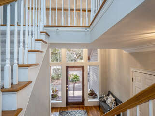 The front foyer is flooded with natural light, high ceilings, and opens to the main living spaces.