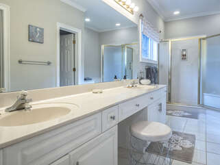 The master bath has double vanities, a walk-in shower, and Jacuzzi tub.