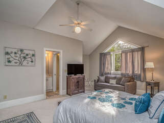 There is a comfortable seating area for reading or television watching in this bedroom.