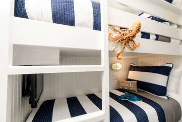 Look how cute these bunks are! Custom built to be as wide as possible (more narrow than twin). There is also a built-in TV and Smart Blu-ray player on the bottom bunk with Netflix provided!!