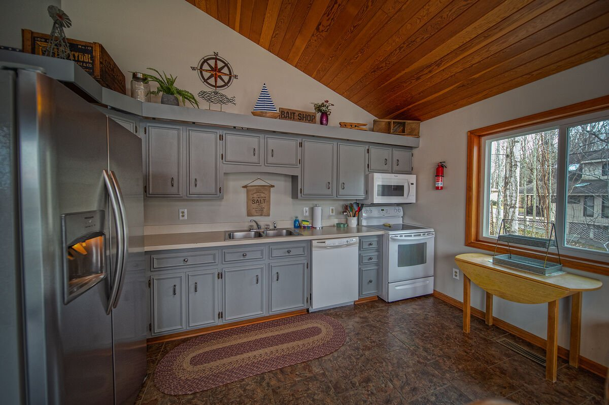 Kitchen with Lake View, Refrigerator, Microwave, and Dishwasher.